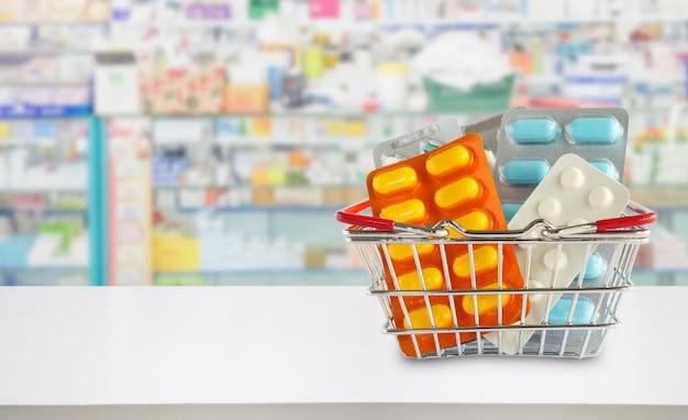 Medizinpillenpaket im einkaufskorb mit apotheken-drogerie-regalen