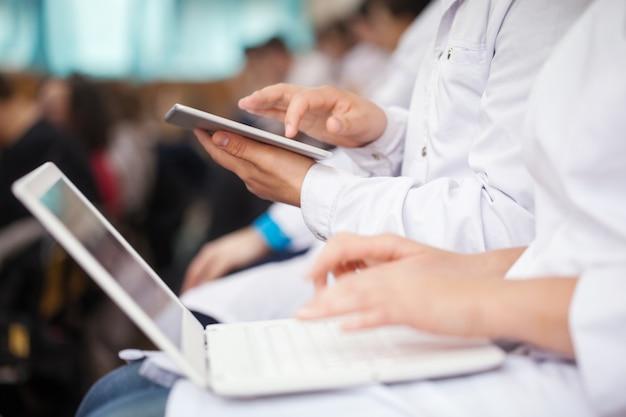 Medizinstudenten mit auflage und laptops im auditorium