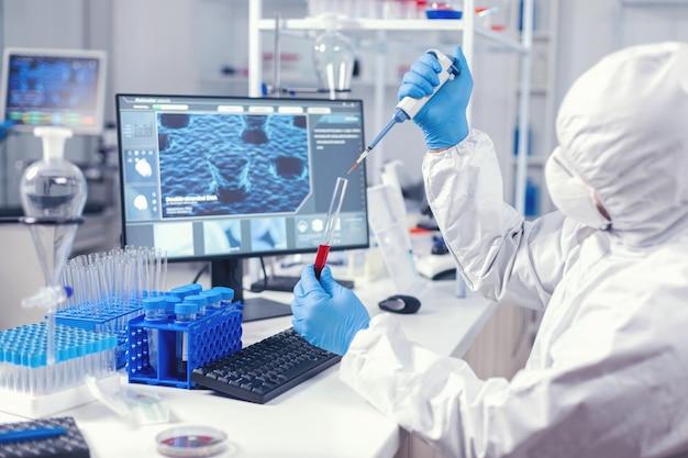 Medizintechniker, der spender verwendet, um blutprobe aus reagenzglas im labor zu entnehmen