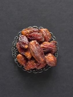 Medjool datteln früchte in einer schüssel auf einem dunklen tisch. ansicht von oben.