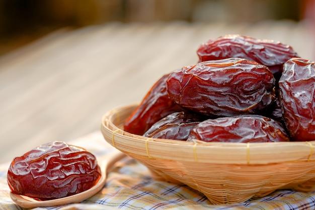Medjool-datteln oder dattelfrucht im holzkorb und löffel auf dem tisch