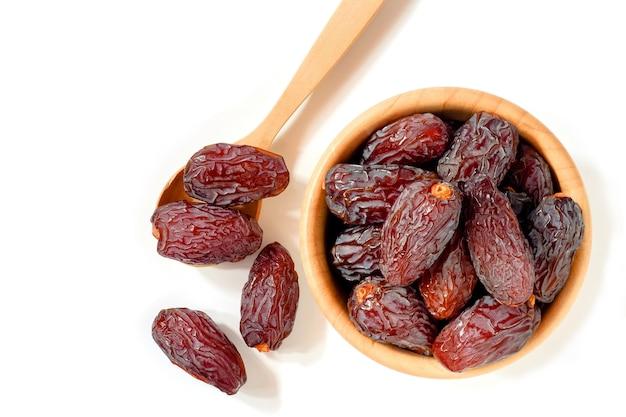 Medjool-datteln oder dattelfrucht in holzbechern und -löffeln auf weißem hintergrund isolieren