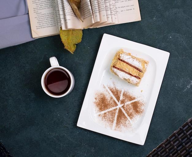 Medovik-kuchen mit kakaopulver und einer tasse tee auf der steintabelle. ansicht von oben.