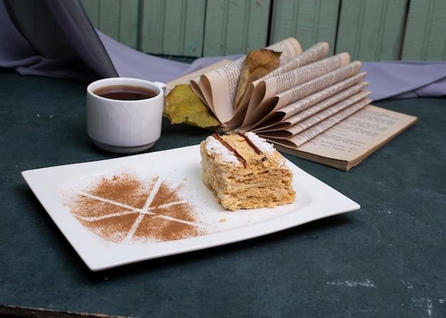 Medovik-kuchen mit kakaopulver und einer tasse tee.