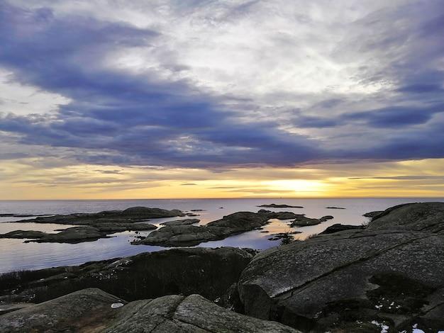 Meer umgeben von felsen unter einem bewölkten himmel während des sonnenuntergangs in rakke in norwegen