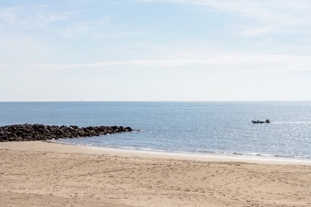 Meer und strand mit fischerboot am sommermorgen