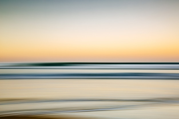 Meer während eines bunten sonnenuntergangs mit einem bewegungseffekt - ein cooles bild für tapeten und hintergründe