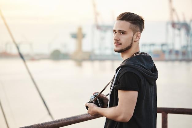 Meer zieht diesen fotografen an. außenporträt des attraktiven jungen kerls, der im hafen steht und das betrachten des meeres beim halten der kamera genießt, auf der suche nach einem guten ort zum fotografieren, beiseite schauen