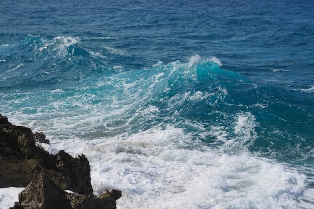 Meerblick, der wellen auf schwarzem lava rock bricht. küstenlinie mit der türkiswelle, die auf lavafelsen bricht