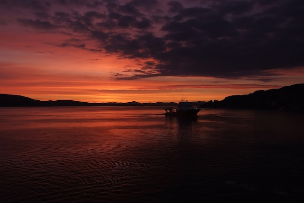 Meerblick nach sonnenuntergang in bergen, norwegen. schiff in der abenddämmerung im meer. drastischer himmel über sonnenuntergangmeerwasser. reisen mit abenteuern per schiff. sonnenaufgang. schönheit der natur. fernweh und urlaub.