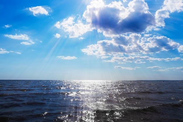 Meerblick unter blauem himmel mit wolken, sonnenstrahlen durch die wolken, schöner sonniger meerblick.