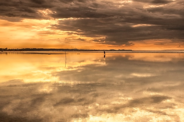 Meerblickansicht des sonnenuntergangs auf dem langen strand mit reflex auf dem sandstrand