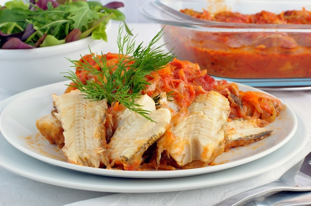 Meeresfisch überbacken mit zwiebeln und karotten in tomatensauce
