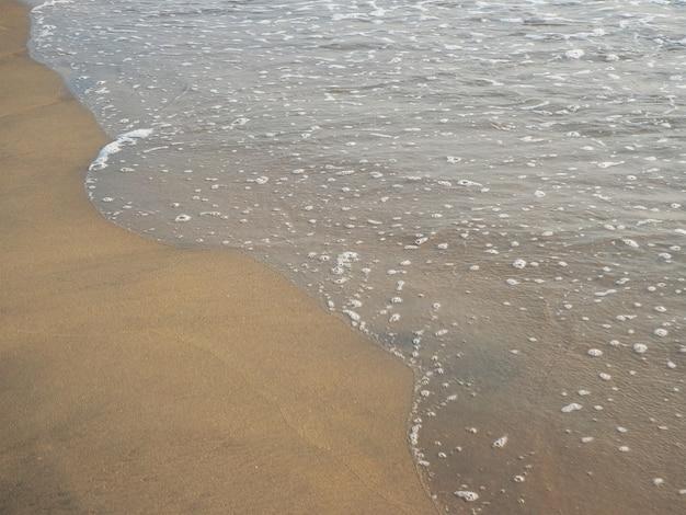 Meeresflut an einem sandstrand tagsüber im sommer im urlaub