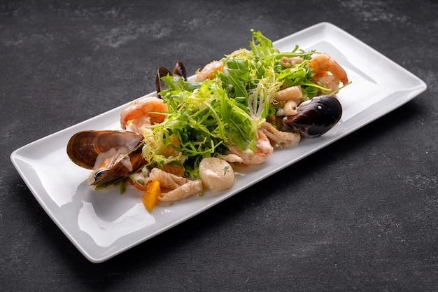 Meeresfrüchte auf einem teller, muscheln, jakobsmuschel, garnelen, tintenfisch, mit salatmischung auf dunklem hintergrund