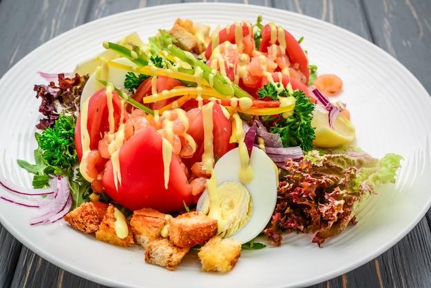Meeresfrüchte-caesar-salat mit garnelen, salatblatt, croutons, cherry tomato und käse