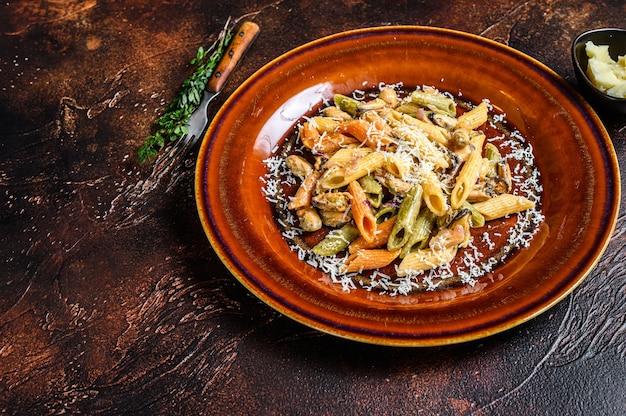 Meeresfrüchte farbe penne pasta in sahnesauce auf einem teller. dunkler hintergrund. draufsicht. speicherplatz kopieren.