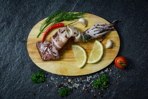Meeresfrüchte gegrillter kalmar mit kräutern und gewürzen zitronentomate-chili-knoblauch und dill auf schneidebrett