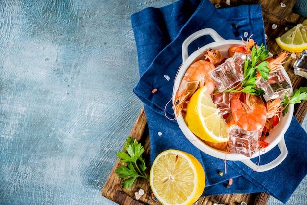 Meeresfrüchte, gekochte garnelen mit zitrone und eis auf einem hellblauen hintergrund