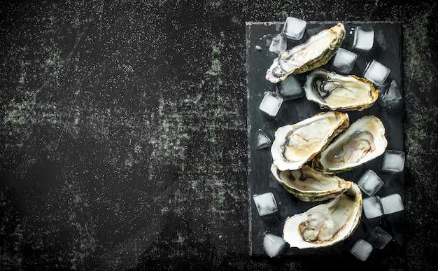 Meeresfrüchte. geöffnete rohe austern auf einem steinbrett mit eiswürfeln. auf dunklem rustikalem hintergrund