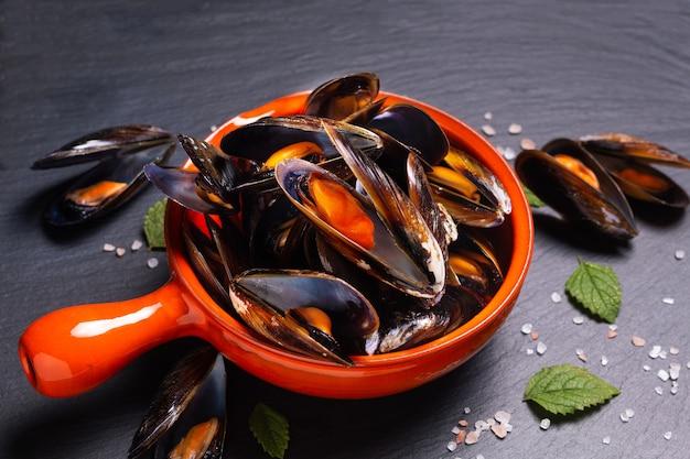 Meeresfrüchte-konzept muscheln in der orangefarbenen griffschale auf schwarzem schieferstein mit kopienraum