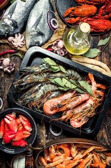 Meeresfrüchte mit gewürzen auf einem holztisch.