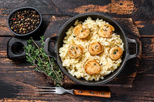 Meeresfrüchte-risotto mit jakobsmuscheln in einer pfanne. dunkler hölzerner hintergrund. ansicht von oben.