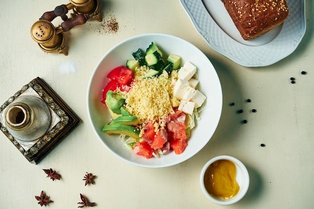 Meeresfrüchte-schüssel mit avocado, couscous, lachs, tomate. buddha-schale mit gesundem und ausgewogenem essen. draufsicht, flach liegen