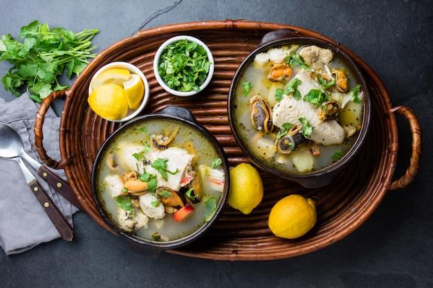 Meeresfrüchtefischsuppe in tonschalen, serviert mit zitrone und koriander.