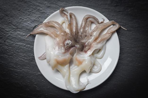 Meeresfrüchtekalmar auf weißer platte roher kalmar des frischen krakenozean-feinschmeckers auf dunkler oberfläche