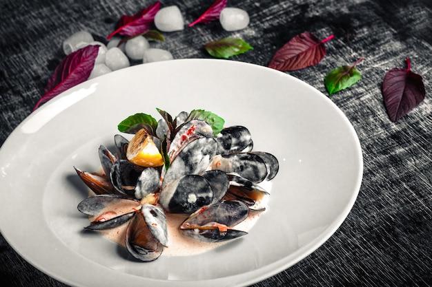 Meeresfrüchtemiesmuscheln in sahnesauce mit zitrone und basilikum auf einem schwarzen kreidebrett