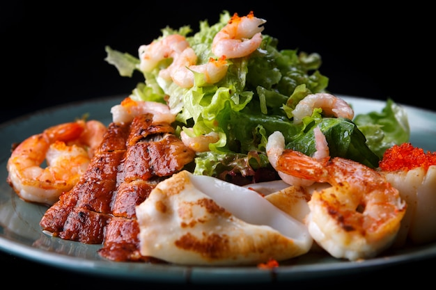 Meeresfrüchtesalat. garnelen, aal, tintenfische, salat. vor einem dunklen hintergrund.