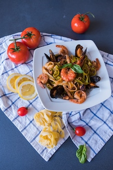 Meeresfrüchteteigwaren mit miesmuscheln und garnele auf weißer platte. spaghetti auf blauem hintergrund