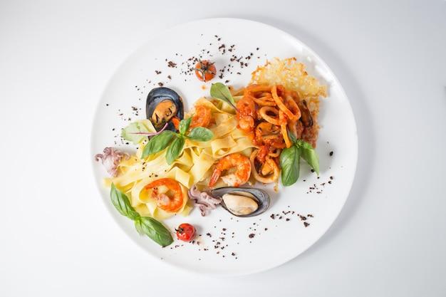Meeresfrüchteteigwaren mit muscheln, tintenfisch, garnelen, tomaten und grün