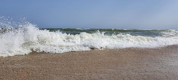 Meereslandschaft. azurblaues wasser, schäumende wellen am ufer. selektiver fokus.