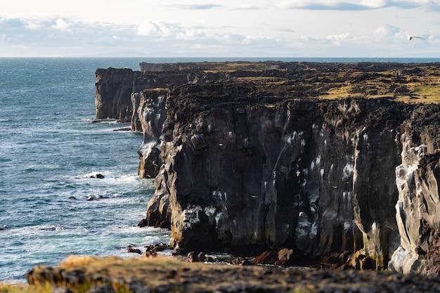 Meereslandschaft mit gefährlicher vertikaler klippe, wolkenlandschaft während des sonnenuntergangs