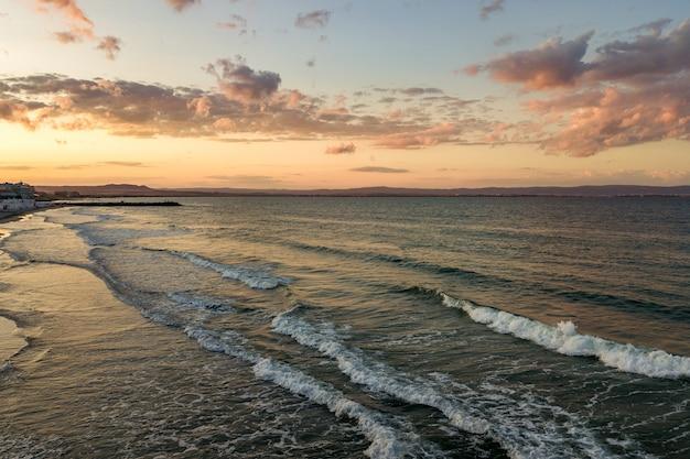 Meeresoberfläche mit blauen wasserwellen unter gelbem und lila sonnenuntergangshimmel.