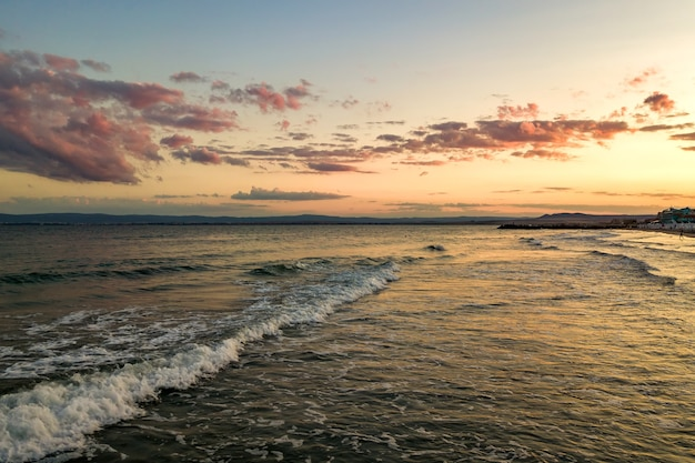 Meeresoberfläche mit blauen wasserwellen unter gelbem und violettem sonnenuntergangshimmel.