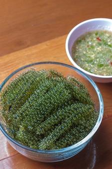 Meerespflanzensalat auf einem bretterboden mit meeresfrüchtesoße. meeresalgen, gesunde ernährung der seetrauben.