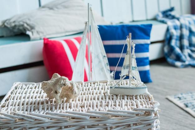 Meeresstillleben mit schiffen und korallenstück. antikes segelboot spielzeugmodell und farbiges gestreiftes kissen
