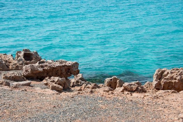 Meeresufer mit felsen und klarem transparentem meerwasser. natürlicher meereshintergrund. blaue ozean-tapete, meereswelle am sonnentag. kristallklares wasser und orangefarbene klippen des tropischen meeres