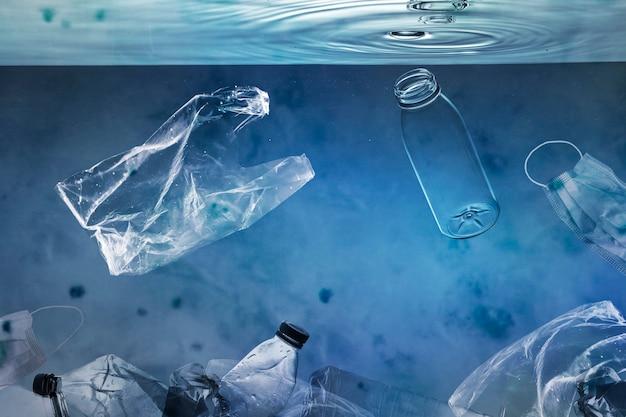 Meeresverschmutzungskampagne mit schwimmenden plastiktüten und gebrauchten flaschen bottles