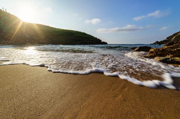 Meereswelle nähert sich dem strand mit blick auf den sonnenuntergang hinter einem berg santander