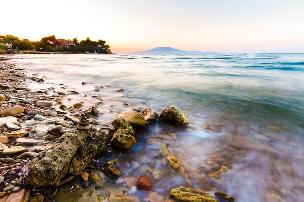 Meereswellen auf dem steinstrand bei sonnenuntergang, zakynthos, griechenland