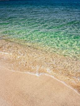 Meereswellen des blauen transparenten wassers auf sandigem strand