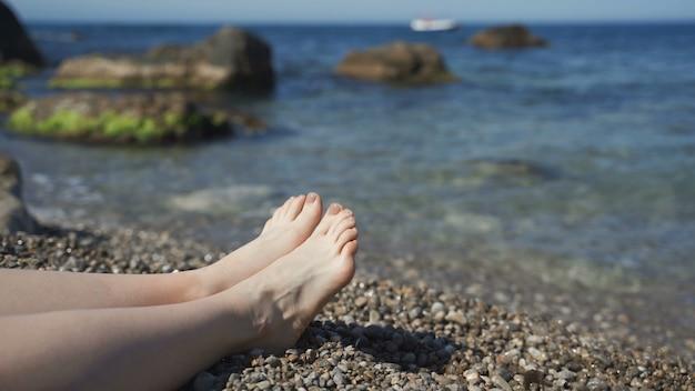 Meereswellen, die über gebräunten weiblichen füßen waschen. schöne junge frau, die auf küste während der sommerferien entspannt. beine des mädchens, das an einem sonnigen tag am strand liegt. nahaufnahme zeitlupe