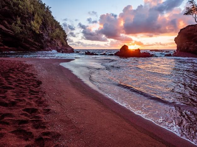 Meereswellen, die während des sonnenuntergangs an land abstürzen