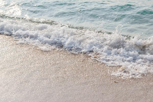 Meereswellen schlagen den strand, licht fällt auf die meeresoberfläche