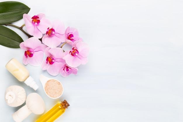 Meersalz, aromaöl in flaschen und orchidee auf weinlesehintergrund.