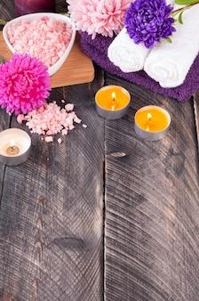 Meersalz, handtuch, duftkerze und blumen für spa-behandlungen auf altem holzhintergrund